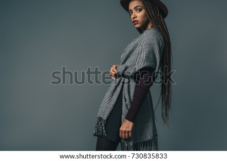 Stock Photo stylish african american girl in hat looking at camera while posing isolated on grey