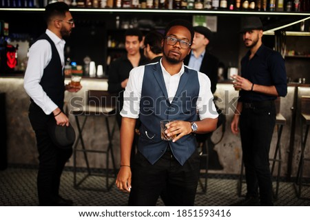 Photo of  Stylish african american man against group of handsome retro well-dressed guys gangsters spend time at club, drinking on bar counter. Multiethnic male bachelor mafia party in restaurant.