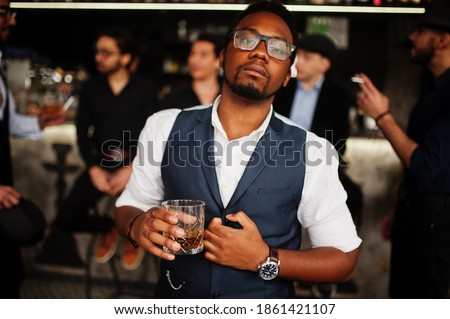 Stylish african american man against group of handsome retro well-dressed guys gangsters spend time at club, drinking on bar counter. Multiethnic male bachelor mafia party in restaurant. Stock photo ©