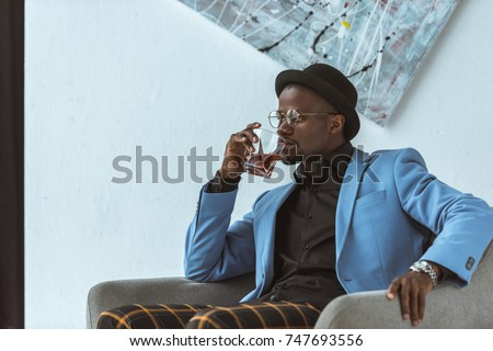 stylish african american man in hat and blue jacket sitting in armchair and drinking whiskey #747693556