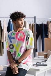 Stylish african american showroom proprietor standing near table