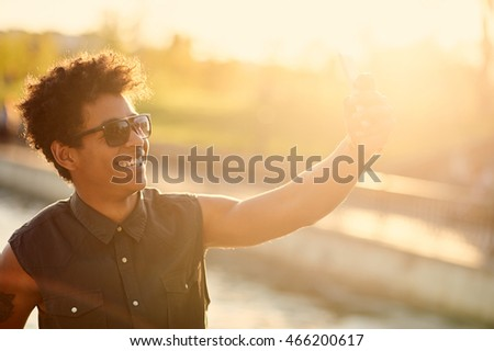 stylish african american young man making a selfie on sunset background with sun flare. Warm autumn colors concept #466200617
