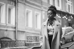 Stylish African girl in the blue coat on the street with bokeh in the background black and white image