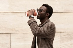 Stylish african man drinking coffee on the run wearing brown knitted cardigan and sunglasses on city street over brick wall background