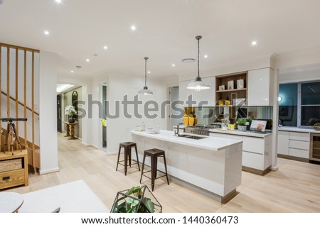Stylish all-white kitchen counters and cabinets with a snack counter with two stools and contemporary style hanging lamps. #1440360473