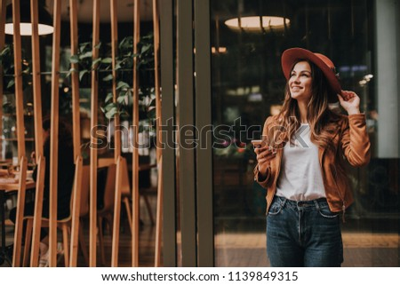 Stylish and amazing girl is holding the edge of hat and looking up. She is smiling. Girl is holding phone in hand nd posing. Woman looks happy #1139849315