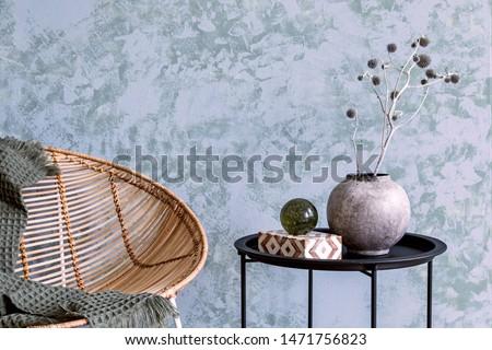 Stylish and boho composition of living room with design armchair, black coffee table, vase with flowers, abstract background walls and elegant accessories. Modern, minimalistic home decor. Template.