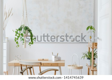 Stylish and boho home interior of living room with wooden desk, chair and shelf. Design and elegant accessories. Botany home decor with a lot of plants and plant stand. Abstract painting on the wall.