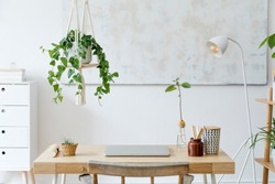 Stylish and boho home interior of open work space with wooden desk, chair, lamp, laptop and white shelf. Design and elegant personal accessories. Botany and minimalistic home decor with plants.