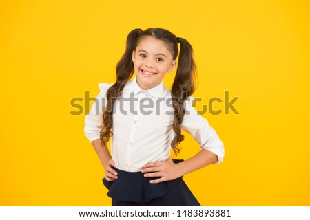 Stylish and chic. Stylish schoolgirl. Happy little child with stylish look on yellow background. Small girl with long hair smiling in stylish school uniform.
