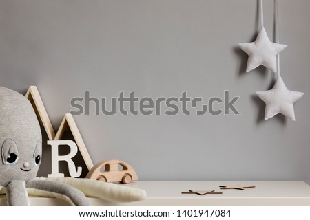 Stylish and cozy childroom with plush octopus, wooden mountain box, car and hanging white stars on the gray wall. Bright and sunny interior. Copy space. Minimalistic childish decor. Template.