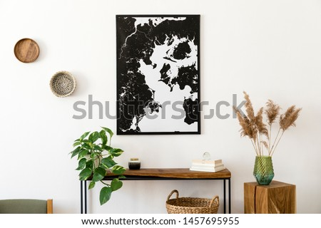 Stylish and cozy scandinavian interior of living room with wooden console, rings on the wall, cube, plants and elegant personal accessories. Black mock up poster map. Design home decor. Template.