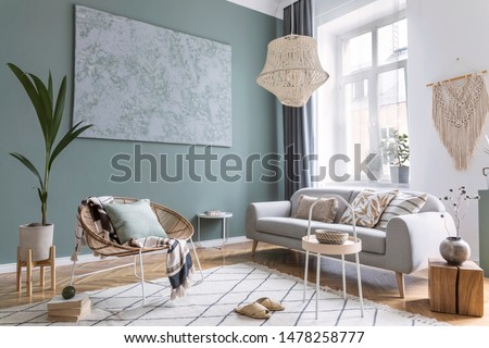 Stylish and design composition of living room with gray sofa, rattan armchair, cube, plaid, pillows, tropical plants, macrame and elegant accessories. Stylish home decor. Bright interior. Template.