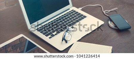 Stylish and elegant composition for business negotiations or website design. Wireless charging for the smartphone, keyboard, wallet, steel pen and glasses lie on a stylish vintage dark desk. #1041226414