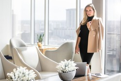 Stylish and elegant, sophisticated fashionable businesswoman in classy business executive outfit, posing in luxurious workspace lobby with city skyline backdrop view of buildings