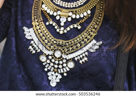 Stylish and fashionable huge golden necklace with rhinestones on chest. Street fashion element.  #503536246