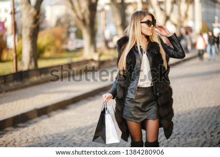 stylish and luxurious girl walking in the autumn city with shopping bags
