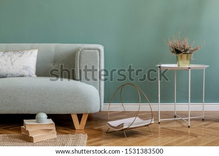 Stylish and minimalistic composition of home interior with mint sofa, pillow, coffee table, flowers, books and elegant accessories. Eucalyptus color concept. Design living room. Template.