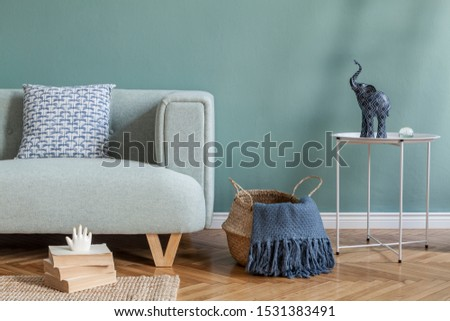 Stylish and minimalistic composition of home interior with mint sofa, pillow, coffee table, rattan basket with plaid, books and elegant accessories. Eucalyptus color concept. Design living room.