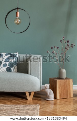 Stylish and minimalistic composition of home interior with mint sofa, pillow, wooden cube, flowers in vase, sculpture and elegant accessories. Eucalyptus color concept. Design living room. Template.