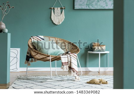 Stylish and minimalistic composition of home interior with rattan armchair, plaid, pillow, macrame, cubes, coffee table, flowers and elegant accessories. Eucalyptus color concept. Design living room.