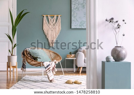 Stylish and minimalistic composition of home interior with rattan armchair, plaid, pillow, sofa, beige macrame, tropical plants, and elegant accessories. Eucalyptus color concept. Design living room.