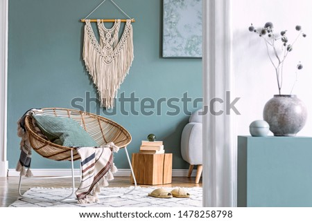 Stylish and minimalistic composition of home interior with rattan armchair, plaid, pillow, wooden cubes, macrame, flowers, books and elegant accessories. Eucalyptus color concept. Design living room.