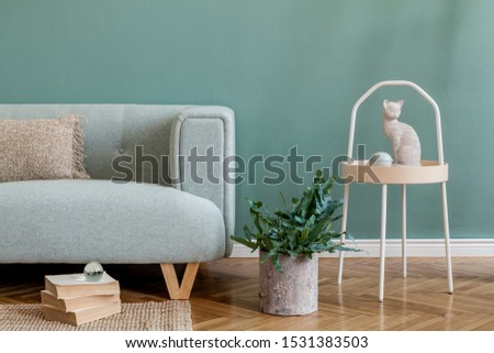 Stylish and minimalistic composition of living room with mint sofa, pillow, coffee table, plant, books, sculpture and elegant accessories. Eucalyptus color concept. Interior design. Template.