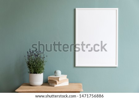 Stylish and minimalistic composition of sitting room with white mock up frame, wooden shelf, lavender in white pot and elegant accessories. Design home decor. Template. Eucalyptus color concept.