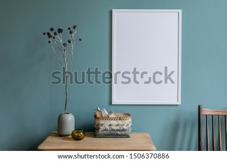 Stylish and minimalistic composition of sitting room with white mock up frame, wooden shelf, flowers in vase, basket and elegant accessories. Design home decor. Template. Eucalyptus color concept.