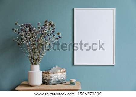 Stylish and minimalistic composition of sitting room with white mock up frame, wooden shelf, flowers in vase , basket and elegant accessories. Design home decor. Template. Eucalyptus color concept.