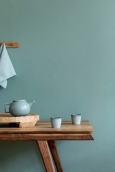 Stylish and minimalistic dining room interior with wooden table, teapot with cups, fruit tray and elegant accessories. Eucalyptus color. Ready to use. Template. Modern home decor. Copy space.