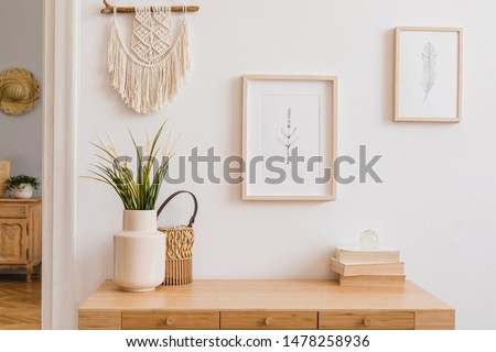 Stylish and modern boho interior of living room with mock up photo frames, flowers in vase, wooden desk, beige macrame and elegant accessories. Design home decor. Bohemian concept. Mockup ready to use Photo stock ©