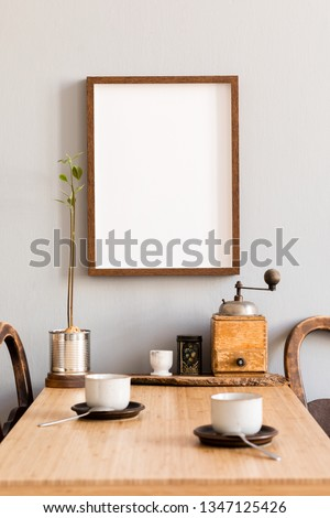 Stylish and modern interior design of kitchen space with small wooden table with mock up photo frame, avocado plant, accessories and cups of coffee. Scandinavian and cozy room decor.