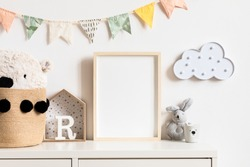 Stylish and modern scandinavian newborn baby interior with mock up photo or poster frame on the white shelf. Toys, teddy bear, plush rabbit and hanging cotton colorful flags and star. Template. Blank.