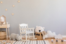 Stylish and modern scandinavian newborn baby interior with toys, children's chair,plush rhino, natural basket with teddy bear and small wooden shelf. Grey background walls with stars pattern.
