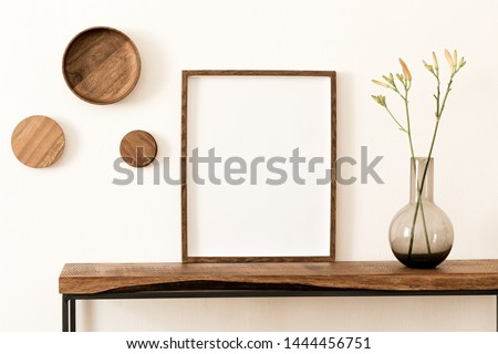 Stylish and modern scandinavian room interior with brown mock up poster frame, wooden console and rings on the wall, beautiful flowers in glassy vase. Design composition of home interior. Home decor.