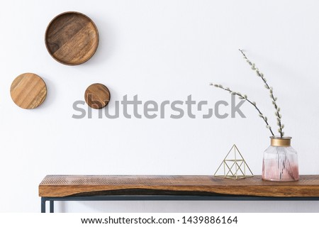 Stylish and modern scandinavian room interior with wooden console and rings on the wall, beautiful flowers in glassy vase. Design composition of home interior. White walls, copy space. Home decor.