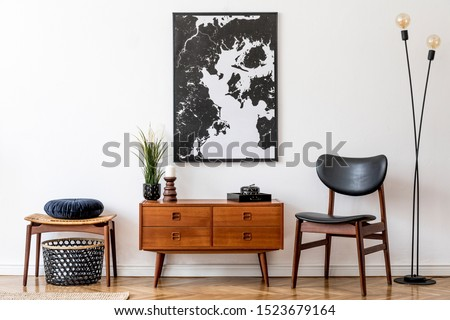 Stylish and retro living room with design vintage wooden commode, chair, footrest, black lamp and elegant personal accessories. Mock up poster map on the wall. Template. Vintage home decor.