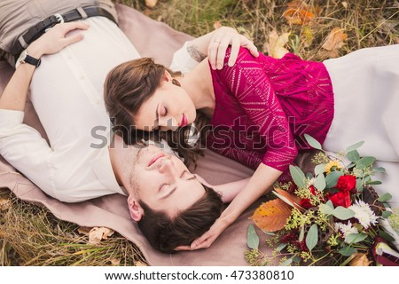 Stylish and romantic caucasian couple lie on the grass and leaves in the beautiful autumn park. Love, relationships, romance, happiness concept.
