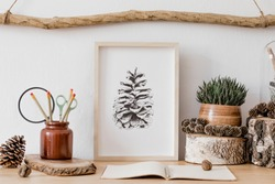 Stylish and scandinavian interior of living room with mock up poster frame, wooden accessories, succulents, forest cones, plants, notes and personal stuff. Minimalistic and botanical home decor.