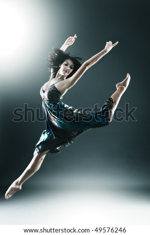 Stylish and young modern style dancer is jumping stretched