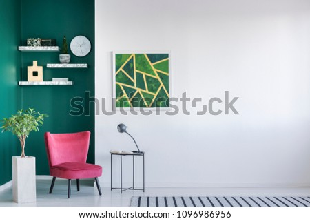 Stylish apartment interior with red armchair, carpet, painting on the white wall, plant in a pot and lamp on the table #1096986956