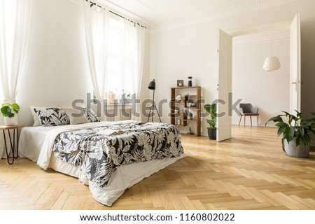 Stylish apartment interior with white walls and herringbone wooden floor. A view from a bedroom with a big bed to another room with an armchair. Real photo.