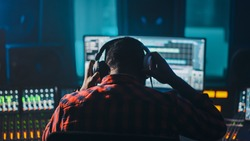 Stylish Artist, Musician, Audio Engineer, Producer Takes Place at His Control Desk in Music Record Studio, Uses Computer Screen show User Interface of DAW Software with Song Playing. Back View