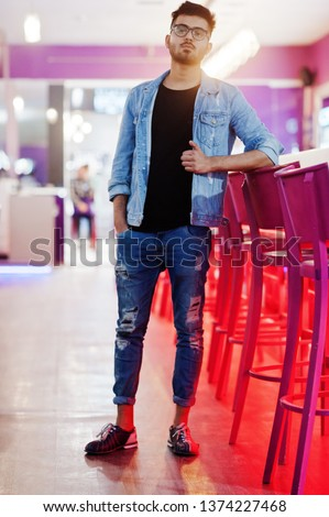 Stylish asian man wear on jeans jacket and glasses posed against bar in club.