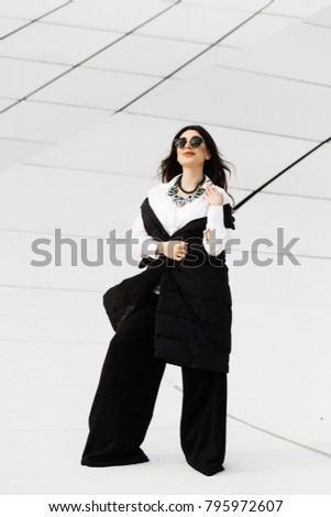 stylish attractive girl in a black suit and sunglasses walking around the city of Baku in Azerbaijan