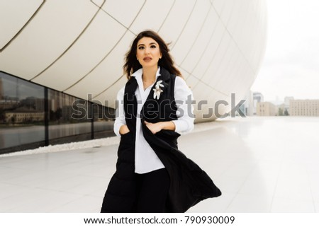 stylish attractive girl in a black suit walks around the city of Baku