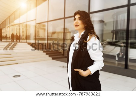 stylish attractive girl in a fashionable black suit posing against the background of unusual buildings in the city of Baku