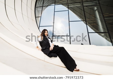 stylish attractive girl in black suit posing against the background of an unusual building in the city of Baku